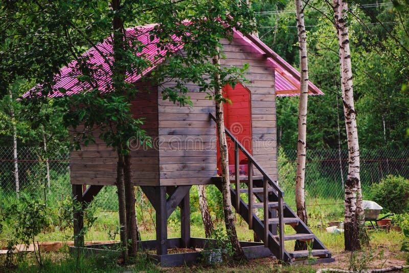 在夏天森林里哄骗有桃红色屋顶的木树上小屋 免版税库存照片