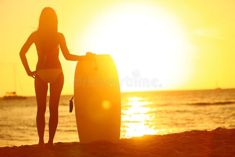 在夏天海滩的日落与身体冲浪者妇女 免版税库存图片
