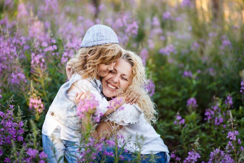 在夏天照顾和一个逗人喜爱的矮小的儿子拥抱和获得乐趣在与花的fild 家庭和幸福概念 免版税库存照片
