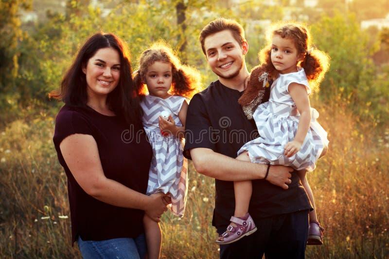 在夏天的本质的愉快的家庭,母亲、父亲和孩子孪生姐妹 卷曲女孩 愉快人微笑 免版税库存图片