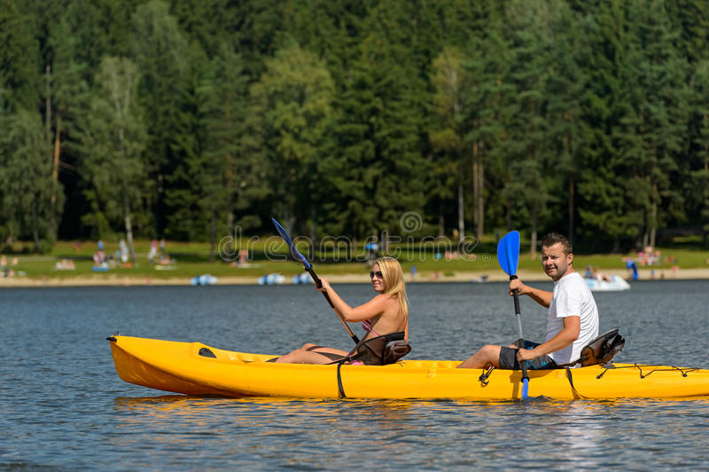 在坐在皮船的池塘年轻夫妇 库存照片