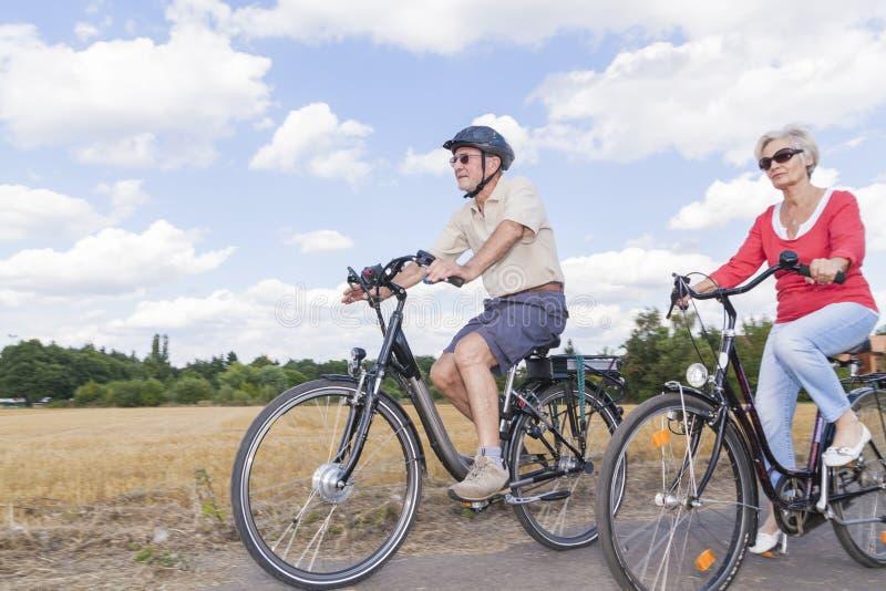 在夏天自行车旅行的资深夫妇 图库摄影