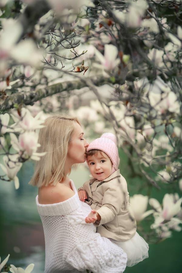 在夏天草甸的愉快的家庭 小女孩儿童拥抱和亲吻母亲的小女儿 免版税库存图片