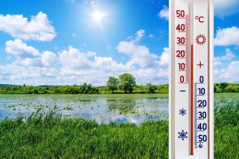 在夏天风景的背景的温度计与一条河的在一好日子显示30度热 夏天heat_ 免版税库存图片
