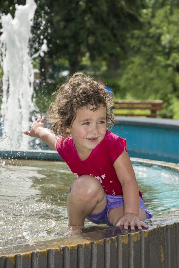 在夏天,在喷泉的女孩戏剧在公园 库存图片