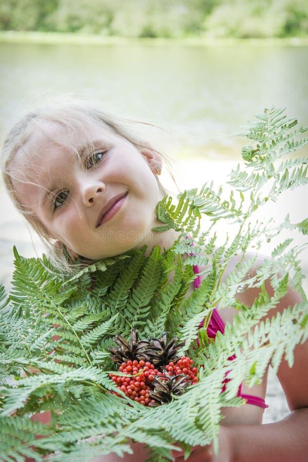 在夏天,在河附近,女孩拿着蕨花束  免版税库存照片
