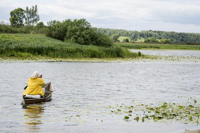 在夏天,妇女女渔翁小船在有a的河漂浮 库存照片