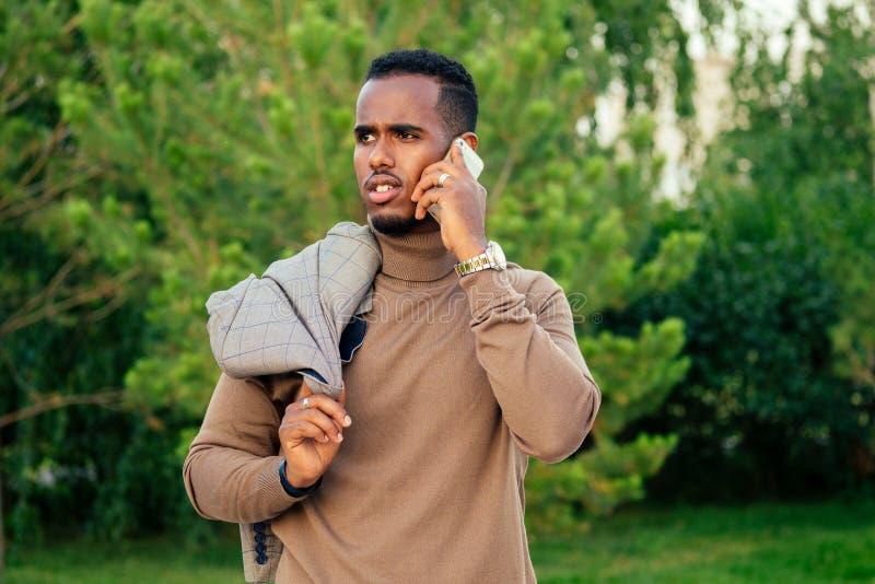 在夏日公园穿着时尚西服的年轻帅气的时尚模特非洲裔美国男子 拉美裔 免版税库存照片