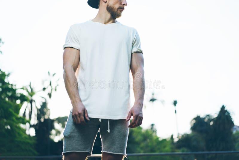 在夏时的照片有胡子的肌肉人佩带的白色空白的T恤杉 绿色城市庭院背景,被弄脏 水平 库存照片