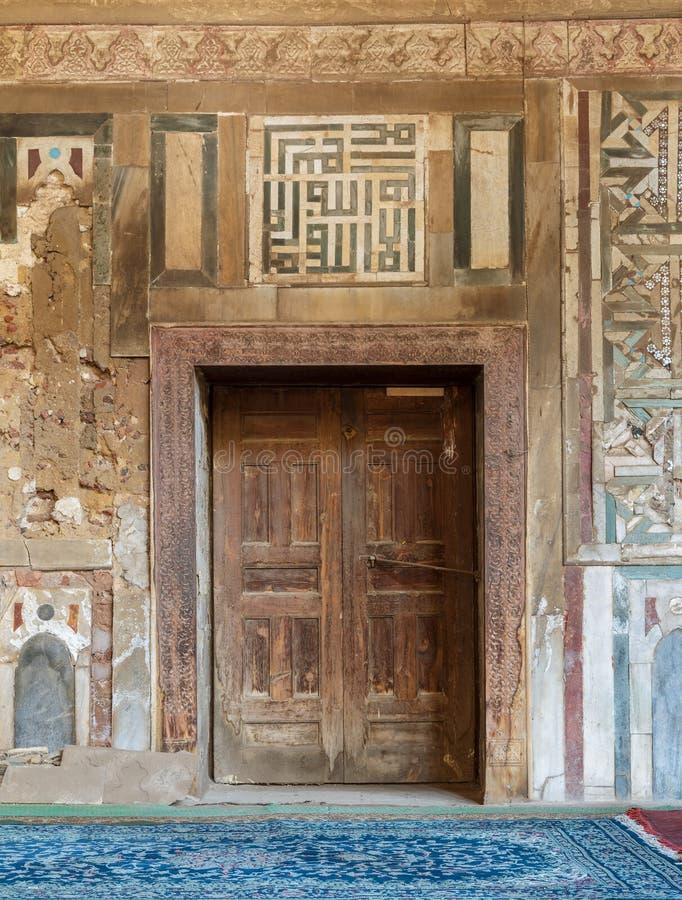 在外在老装饰的大理石墙壁,开罗,埃及上的难看的东西木装饰的门 免版税库存照片