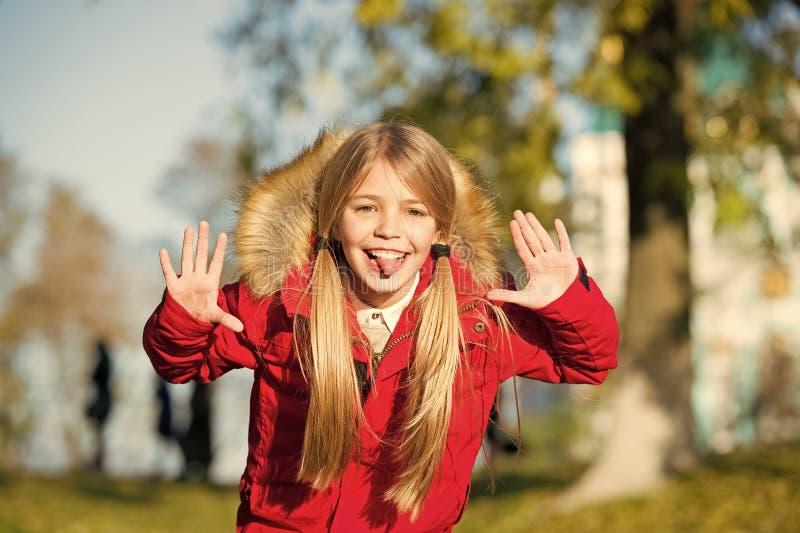 在外套的女孩嬉戏的鬼脸面孔享用秋天公园 嬉戏的孩子休闲 走在温暖的夹克的儿童白肤金发的长发 库存照片