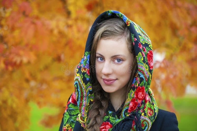 在外套的年轻意大利人和编织在她的头的一条围巾 库存图片