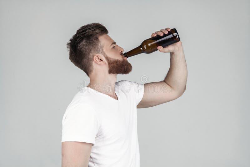 在外形和饮用的啤酒的一个白色T恤身分打扮的一个美丽的性感的有胡子的人的画象,站立  免版税库存图片