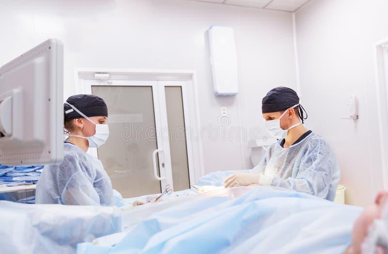 在外科诊所的手术室医治和一个助理 免版税库存照片