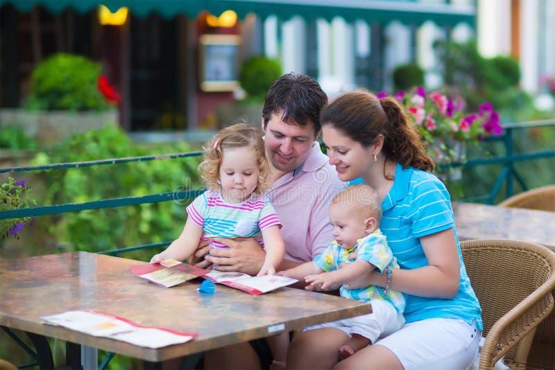 在外部咖啡馆的年轻家庭 免版税图库摄影