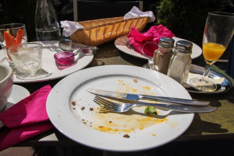在外部膳食以后,桌设置了与一块空的被吃的食物板材 免版税库存照片