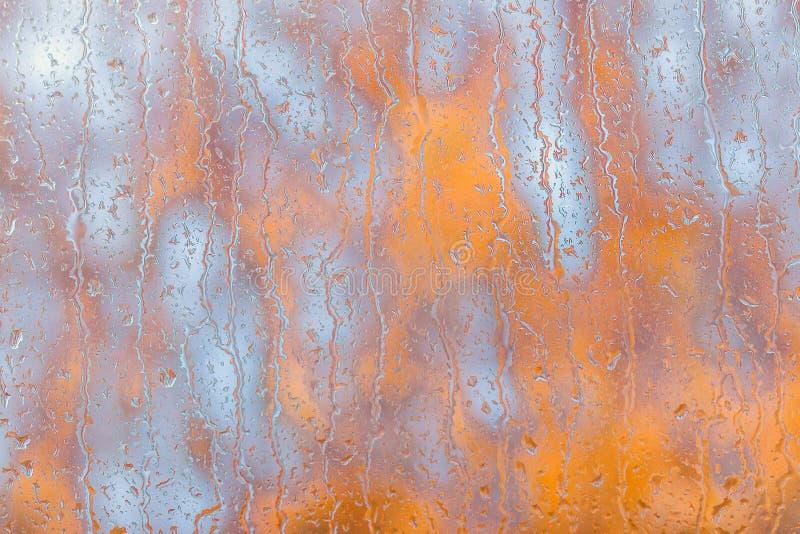 在外面窗口和橙色秋叶的雨珠 免版税库存照片