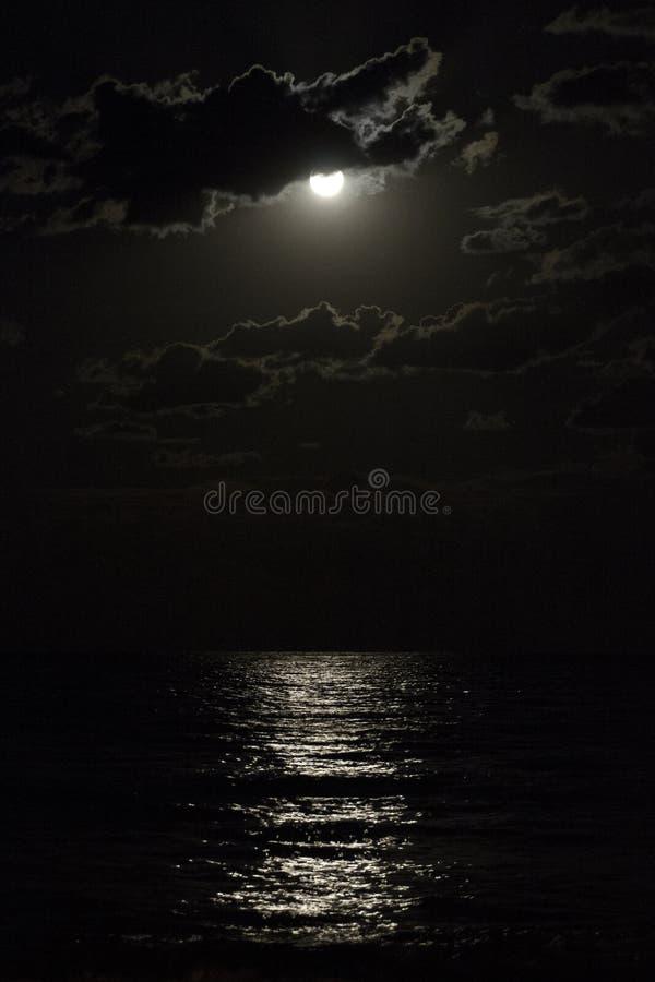 在多云夜空反射的月光的满月在海 免版税库存图片