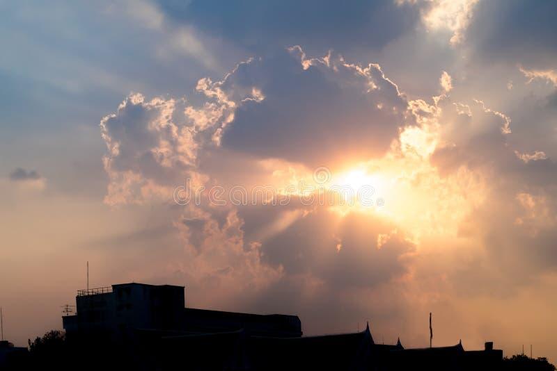 在多云天空后的日落与在大厦,发光的锂的光线 免版税库存图片