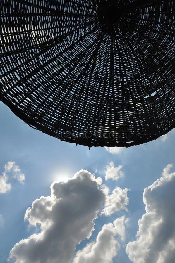 在多云天空背景的伞 库存图片