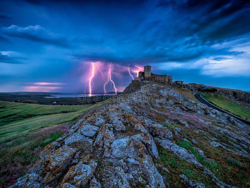 在多云晚上蓝天的雷电闪电在老Enisala堡垒城堡 免版税图库摄影