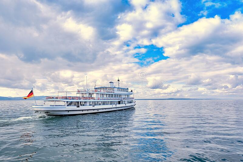 在多云的天空下,渡轮驶过平静的水域 免版税图库摄影