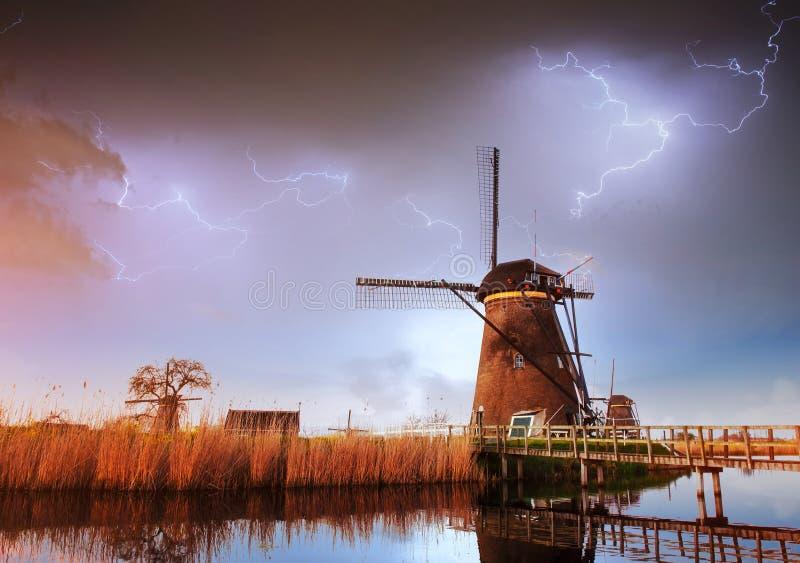 在多云黑暗的天空的闪电 传统荷兰风车运河 免版税库存图片