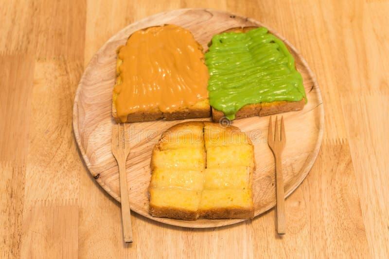 在多士上添面包用黄油,浓缩牛奶,蛋乳蛋糕 免版税库存照片