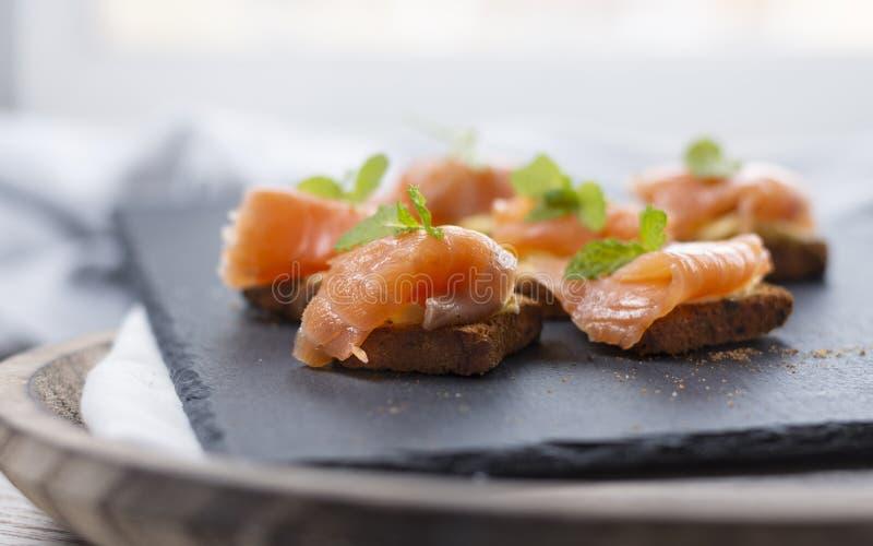在多士的熏制鲑鱼用与薄荷的叶子的黄油在黑石头和老木板-图象 图库摄影