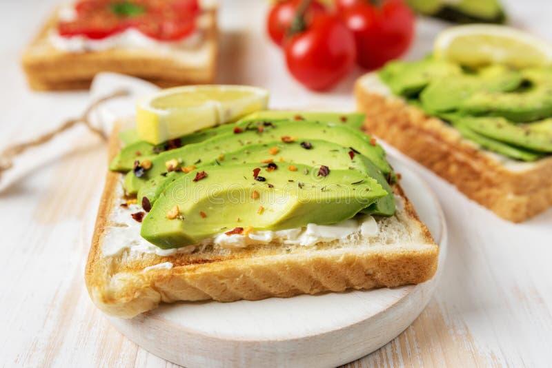 在多士面包的切的鲕梨用在白色木背景的香料 在倾吐的餐馆沙拉的主厨概念食物新鲜的厨房油橄榄 免版税库存图片