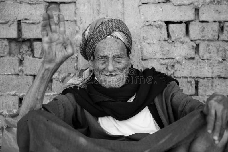 在多孔黏土墙壁的坐的更老的人 免版税库存图片