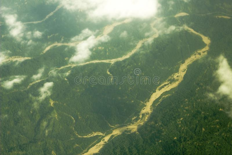 在多小山绿色森林地中的一个含沙河床 在谷的航拍白色云彩 库存图片