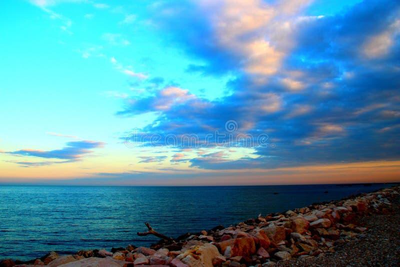 在多岩石的海滩和海的日落天空 免版税库存图片