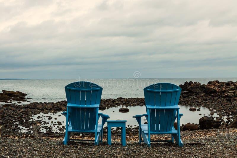 在多岩石的海滩的蓝色木椅子 库存照片