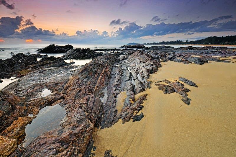 在多岩石的海滩的日出在丹戎附近 库存照片