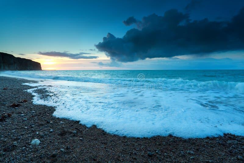 在多岩石的海滩的日落在大西洋 库存照片