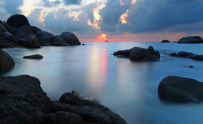 在多岩石的海滩的日落 库存照片