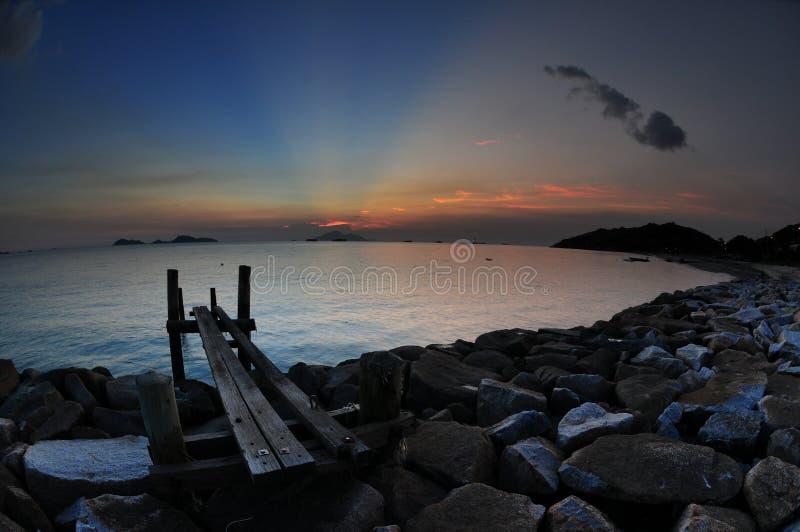 在多岩石的海滩的日落 免版税库存图片