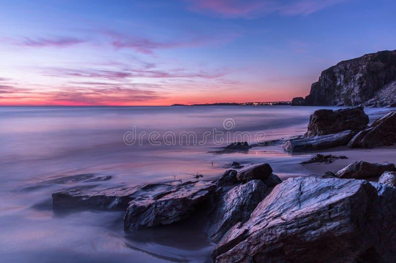 在多岩石的海滩的沿海日落在康沃尔郡,英国 图库摄影