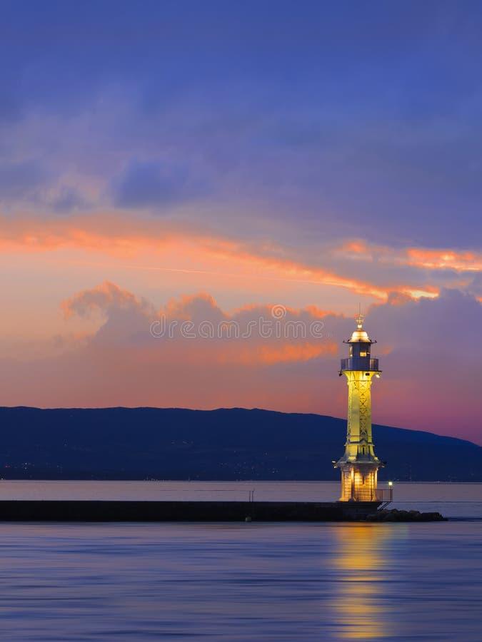 在多彩多姿的剧烈的日落,日内瓦湖,瑞士的金属灯塔 免版税库存图片