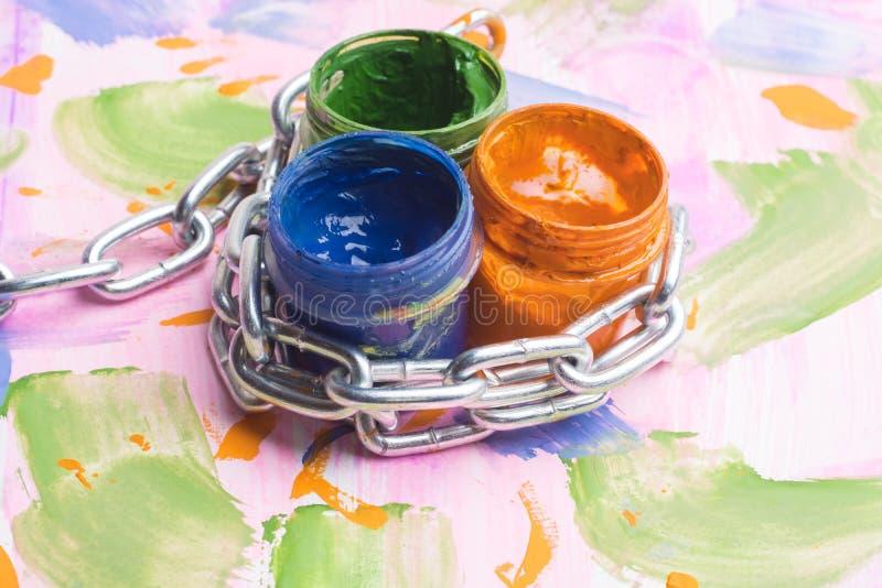 在多彩多姿的背景,有树胶水彩画颜料的瓶子在与三个罐头的一个金属链子被包裹油漆 免版税库存图片