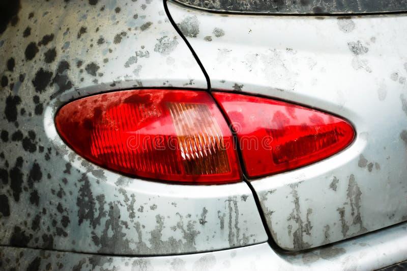 在多灰尘和肮脏的灰色汽车的后面光 库存图片