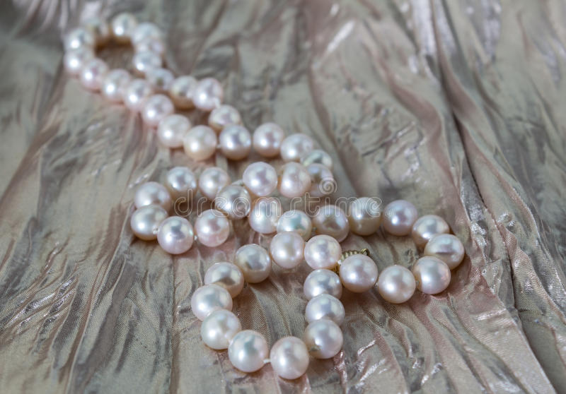 在多灰尘的淡粉红色的桃红色珍珠项链打褶了缎背景 免版税图库摄影