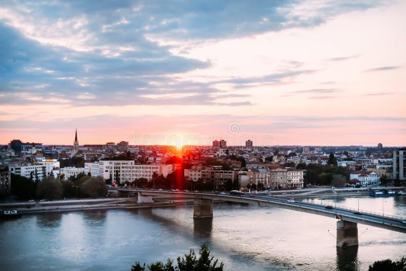 在多瑙河和诺维萨德市的美好的日落有彩虹桥梁的 库存照片