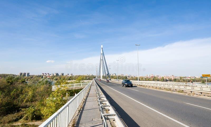 在多瑙河的自由桥梁有海滩和修造的有上面驾车在和天空蔚蓝的诺维萨德市 免版税库存照片