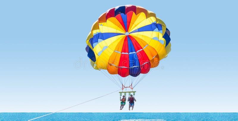 在多米尼加海滩的愉快的夫妇帆伞运动在夏天 夫妇u 免版税库存照片