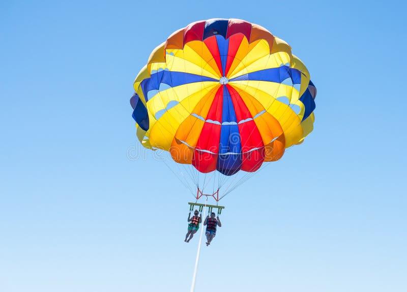 在多米尼加海滩的愉快的夫妇帆伞运动在夏天 在垂悬空中的降伞下的夫妇 儿童有父亲的乐趣一起使用 热带的天堂 POS 免版税库存照片