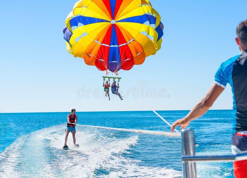 在多米尼加海滩的愉快的夫妇帆伞运动在夏天 夫妇u 免版税库存图片