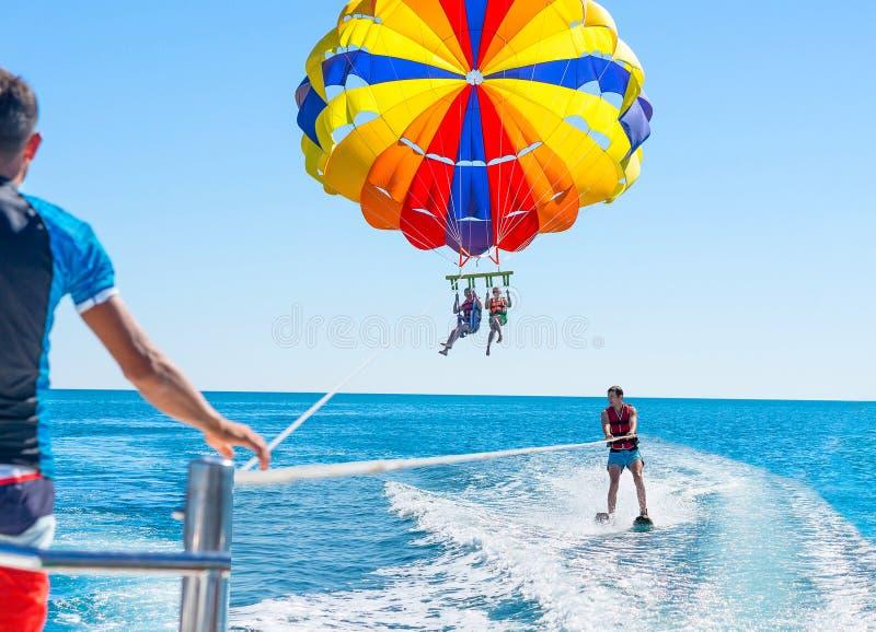在多米尼加海滩的愉快的夫妇帆伞运动在夏天 夫妇u 图库摄影
