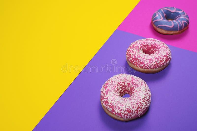 在多色的背景的三个五颜六色的油炸圈饼 图库摄影